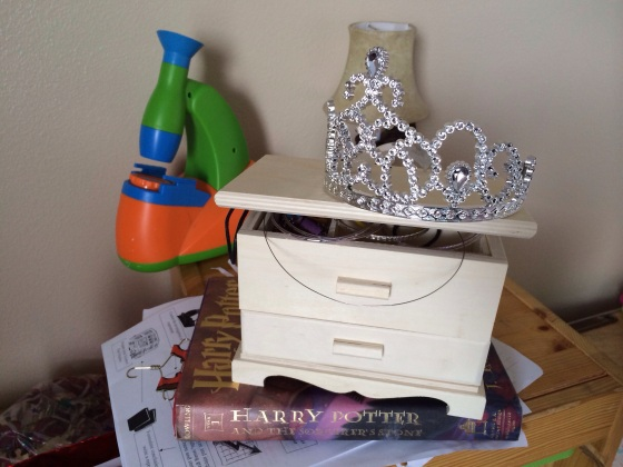 This is a little snapshot of Nola's room.  Harry Potter, a jewelry box, a tiara, and a microscope.  I didn't stage any of that, it's how she had it on her toy organizer.  If you were to turn around you'd see a super tidy bookcase, a ukelele, and a chess set.  I had to avoid stepping on the ukelele on the floor though.